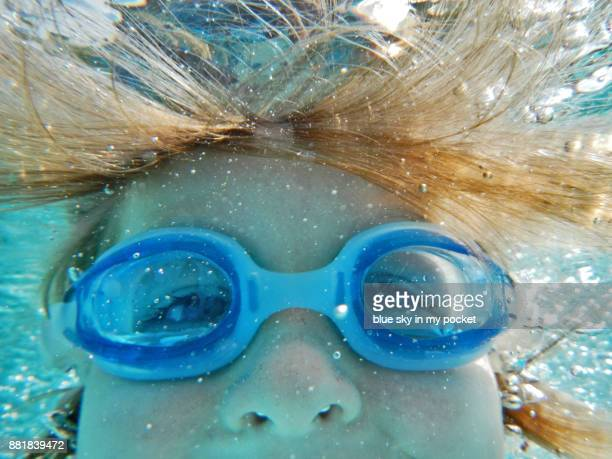 A 5 year old boy swimming underwater.