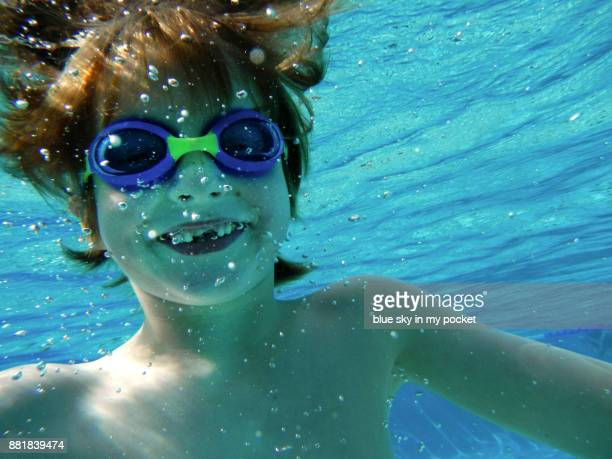A 7 year old boy swimming underwater.