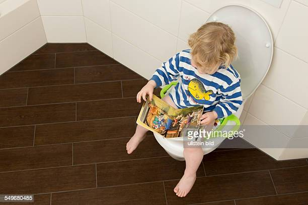 2 year old boy with childrens seat and childrens book on a toilet
