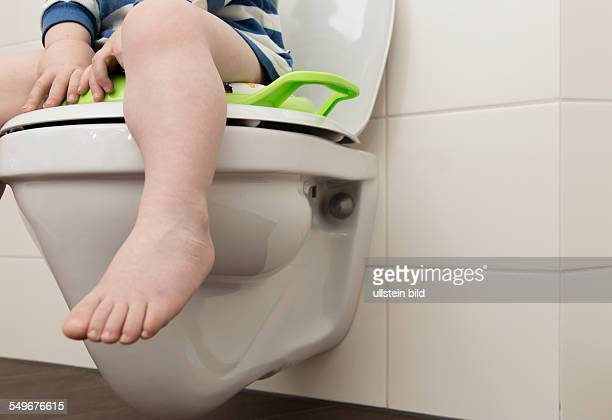2 year old boy with childrens seat on a toilet