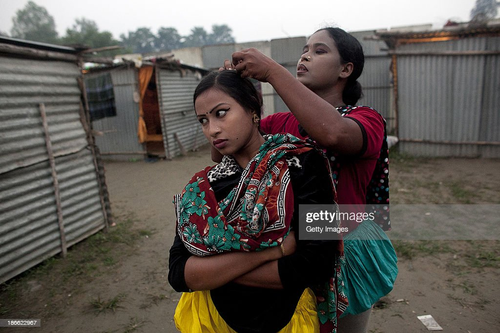 16 year old Bristi Akhter has her hair checked for bugs by her mother, Sheuliy, in the residential area behind the Olympic Circus, October 31, 2013 in Jamsha, Bangladesh. Bristi, was born into the circus. Last month she got married to her cousin last month, dropped out of school when she was 14 years old to start performing. Sheuliy, who doesn't know her age, got married to another circus worker when she was 10 or 11 years old. She never had a chance to go to school. Generations of low income families are born into circuses with rarely the hope of ever working in different profession or escaping the harsh realities of the circus. The children, often very young, are trained to be full working members usually without the opportunity for an education. As modernization slowly takes over landscape of Bangladesh, the circus is a dying art form and is moving further and further away from mainstream entertainment.