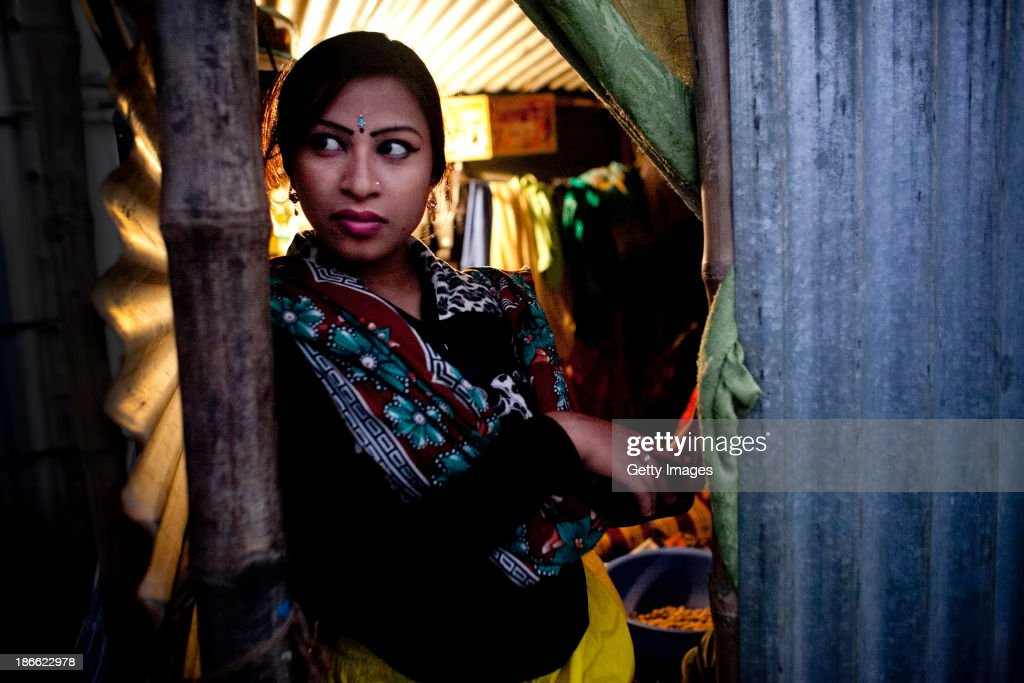 16 year old Bristi Akhter looks out from her makeshift home in the residential area behind the Olympic Circus, October 31, 2013 in Jamsha, Bangladesh. Bristi, was born into the circus. Last month she got married to her cousin last month, dropped out of school when she was 14 years old to start performing. Generations of low income families are born into circuses with rarely the hope of ever working in different profession or escaping the harsh realities of the circus. The children, often very young, are trained to be full working members usually without the opportunity for an education. As modernization slowly takes over landscape of Bangladesh, the circus is a dying art form and is moving further and further away from mainstream entertainment.