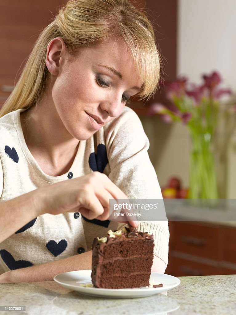 21 year old contemplating chocolate cake : Stock Photo