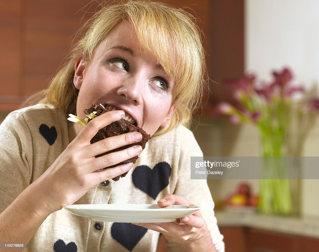 21 year old girl binge eating chocolate cake : Stock Photo