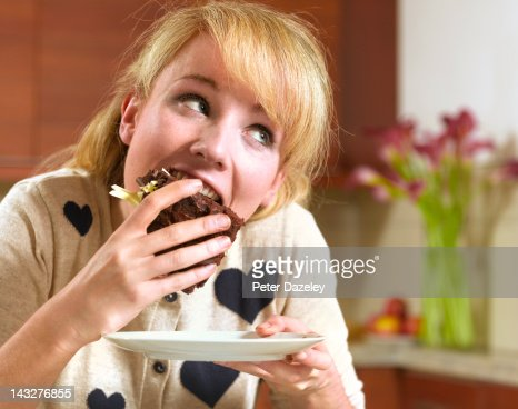 21 year old girl binge eating chocolate cake : Stock Photo