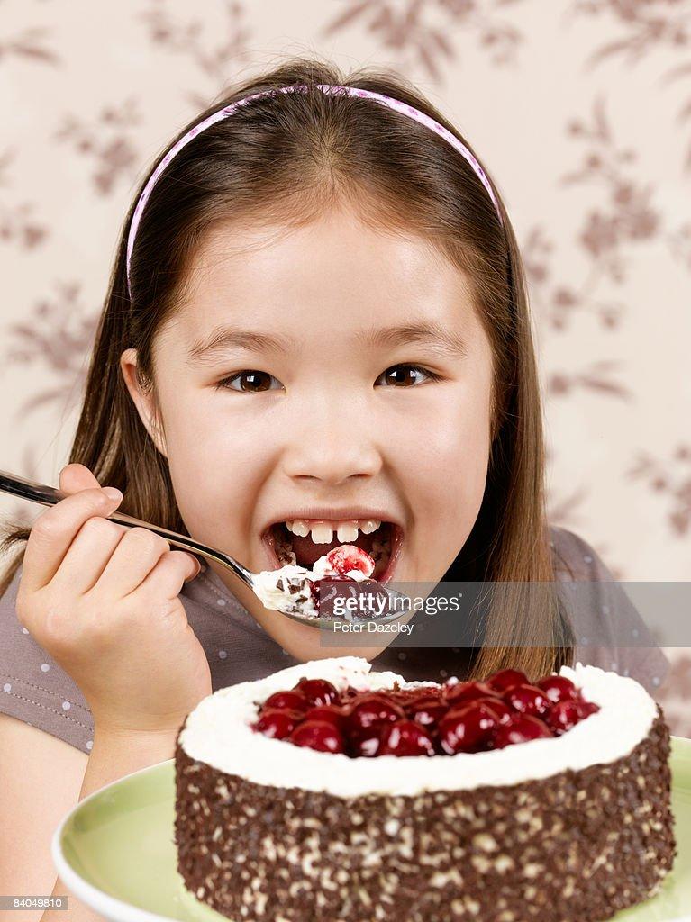 8 year old girl enjoying black forest gateau : Stock Photo