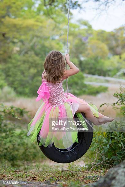 5 year Old Girl in Pink tulle dance costume on tire swing looking away