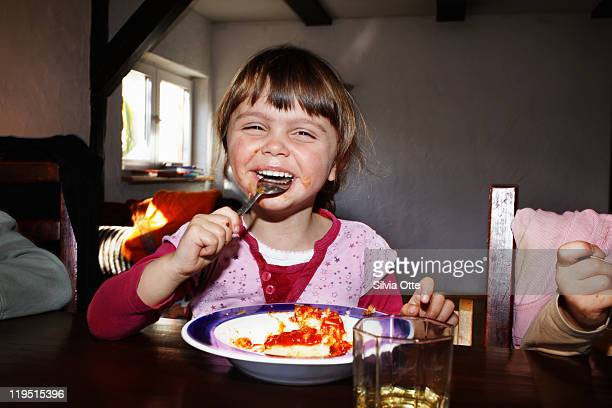 3 year old girl laughing while eating dinner