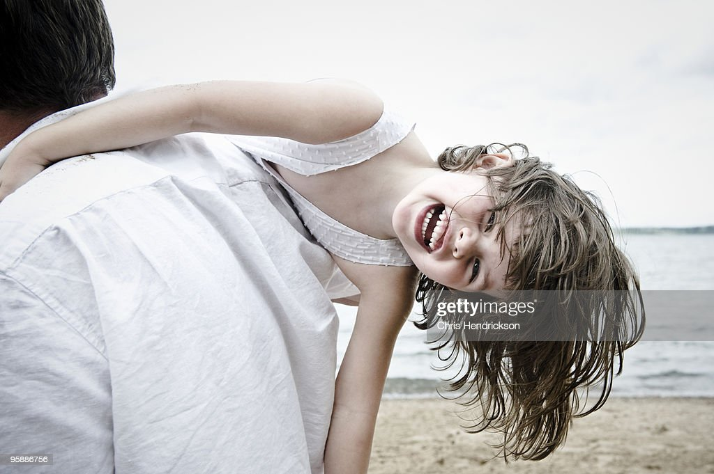 5 year old girl laying on father's shoulders. : Stock Photo