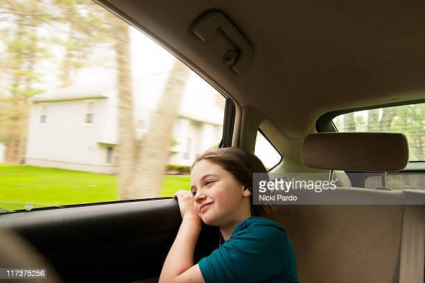 9 year old girl looking out the window of a moving