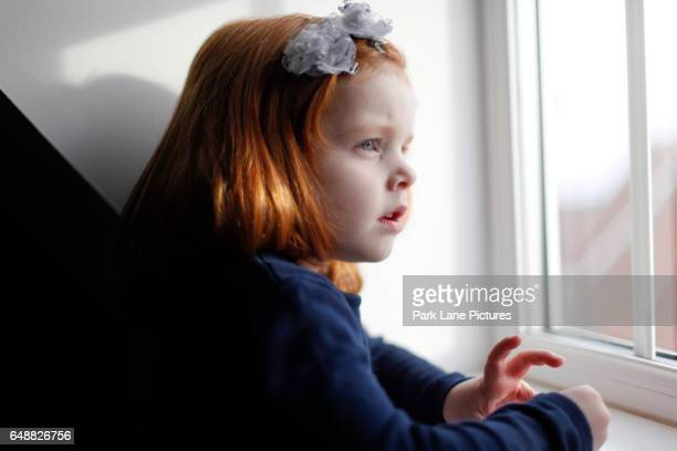 A 4 year old girl with ginger hair looking out of a window