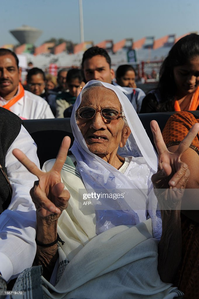 90 year old Hiraba the mother of Chief Minister of the western Indian state of Gujarat Narendra Modi flashes victory signs as she participates in Modi's swearing in ceremony at The Sardar Patel Navrangpura Stadium in Ahmedabad on December 26, 2012. Modi who won a landslide victory in recent state assembly polls, was administered the oath of office and secrecy by Gujarat Governor Kamla Beniwal at a ceremony which was attended by many senior BJP leaders. AFP PHOTO/Sam PANTHAKY