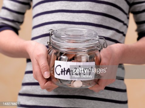 10 year old holding charity donations in a jar