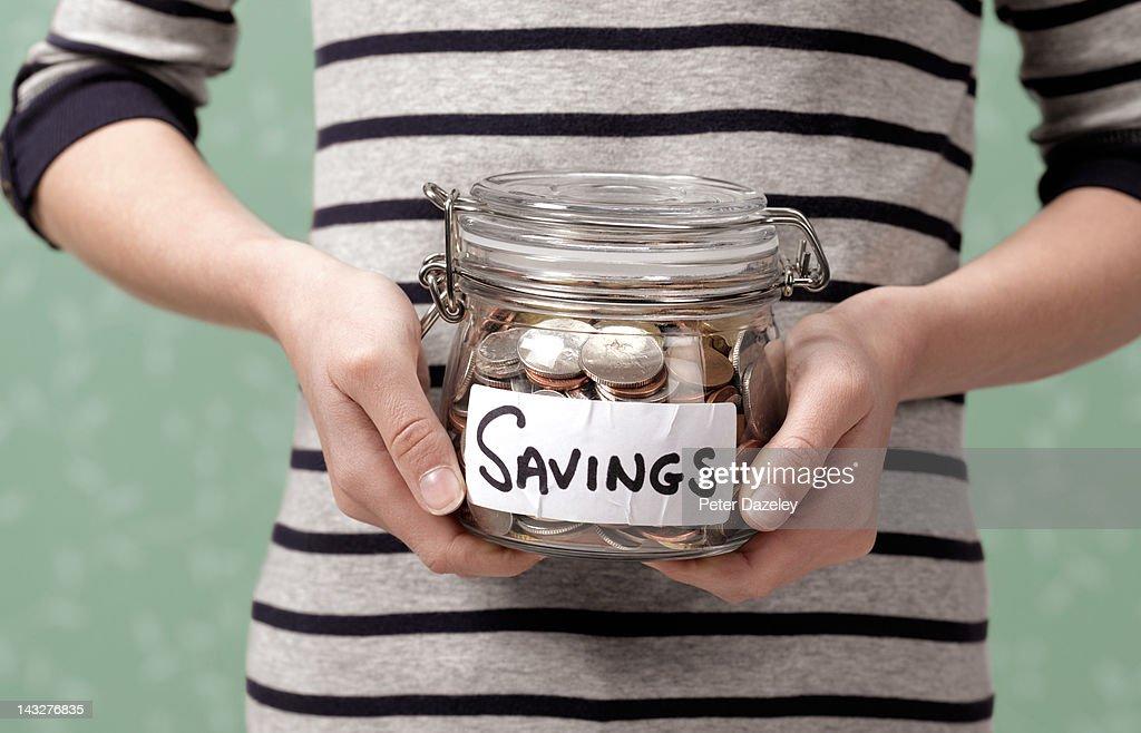 10 year old holding savings in jar : Stock Photo