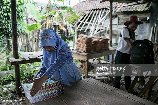 11 year old Indriani Fatmawati helps his father to arrange the books for the mobile library on May 5 2015 in Serang Village Purbalingga Central Java...