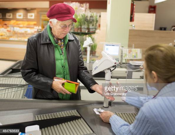 A 75 year old lady paying for her shopping at the check out at a supermarket pictured on October 18 2013 on the island of Borkum Germany Photo by Ute...