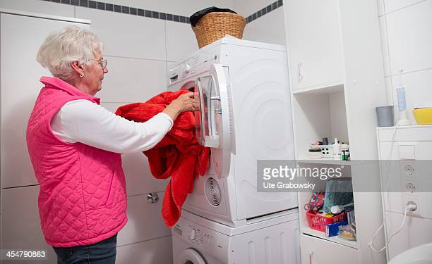 A 75 year old lady putting her washing in the washing machine in the bathroom pictured on October 17 2013 on the island of Borkum Germany Photo by...