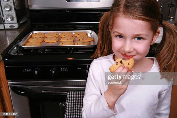 A 5 year old little girl eating a chocolate chip cookie in the kitchen.