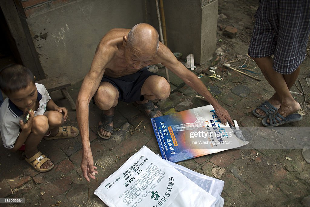 77 year old Lu Zhitian sorts through stacks of medical scans from his lung cancer treatment in a rural village near Fuyang, Anhui Province, China on 28 August 2013. As able-bodied adults seek work in cities in hopes of better income, more and more villages in China are inhabited mostly by the elderly and children.