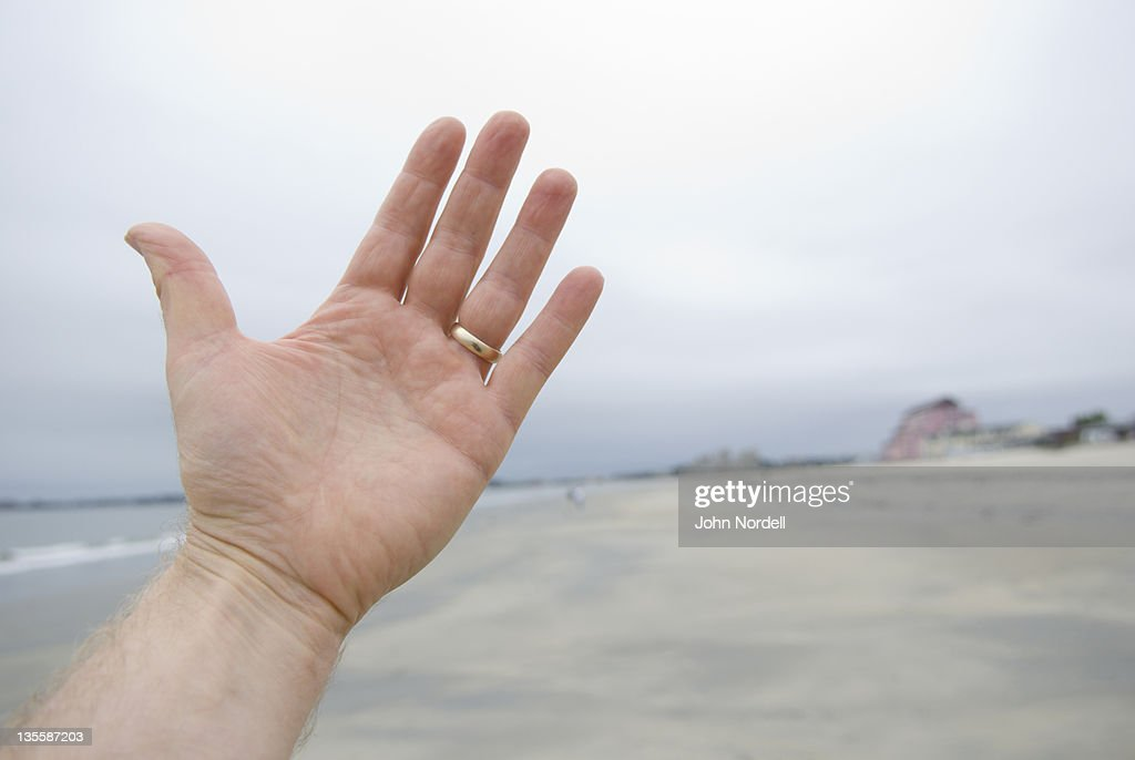 48 year old man holding up his hand at public beach : Stock Photo