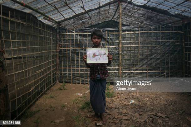 COX'S BAZAR BANGLADESH SEPTEMBER 21 11 year old Manzur Ali poses with his drawing at a CODEC and UNICEF 'child friendly space' on September 21 2017...