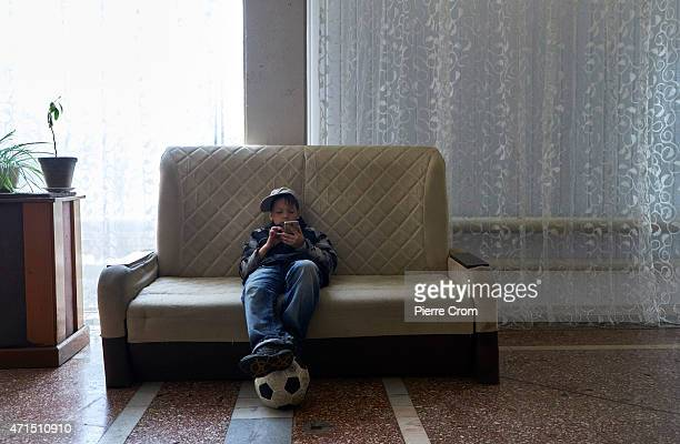 8 year old Misha from Lugansk plays games on a smartphone outside a room where he lives together with his disabled mother on April 29 2015 in Odessa...
