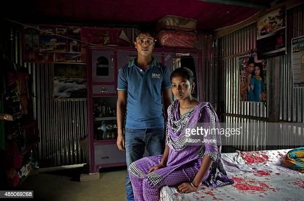 27 year old Mohammad Sujon Mia stands for a photo beside his wife 14 year old Mousammat Akhi Akhter in their home August 19 2015 in Manikganj...