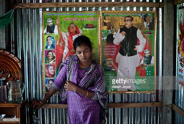 14 year old Mousammat Akhi Akhter stands against a photograph of Bangladesh Prime Minister Sheikh Hasina and her father founding leader of Bangaldesh...