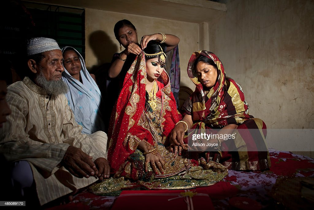 15 year old Nasoin Akhter sits with relatives while posing for photos on the day of her wedding to a 32 year old man August 20 2015 in Manikganj...