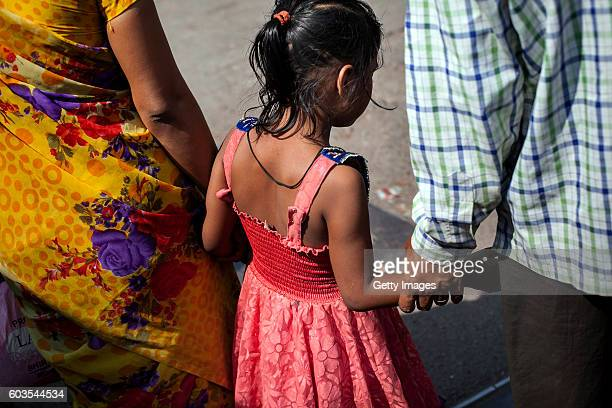 5 year old Nirmala who was raped by her mother's boss holds her parents hands as they walk down the street on November 12 2015 in Maharashtra India...