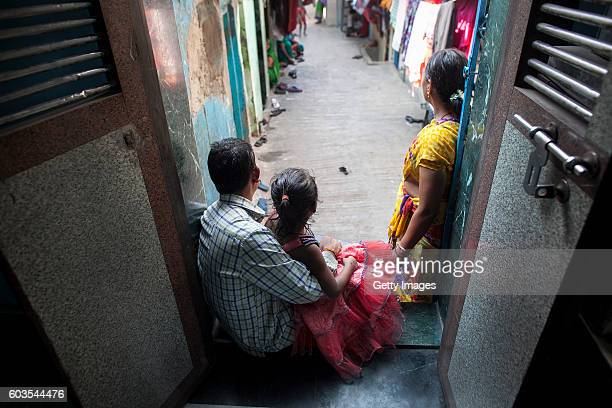 5 year old Nirmala who was raped by her mother's boss poses for a photo with her mother and father on November 12 2015 in Maharashtra India One day...