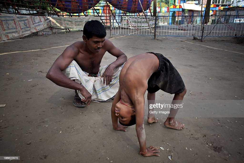 7 year old Nishan practices performing with his father, Mohammad Moshroom, before they work in the Olympic Circus, November 1, 2013 in Jamsha, Bangladesh. Generations of low income families are born into circuses with rarely the hope of ever working in different profession or escaping the harsh realities of the circus. The children, often very young, are trained to be full working members usually without the opportunity for an education. As modernization slowly takes over landscape of Bangladesh, the circus is a dying art form and is moving further and further away from mainstream entertainment.
