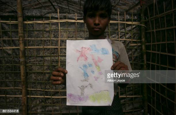 COX'S BAZAR BANGLADESH SEPTEMBER 21 13 year old Nurul Haque holds his drawing at a CODEC and UNICEF 'child friendly space' on September 21 2017 in...