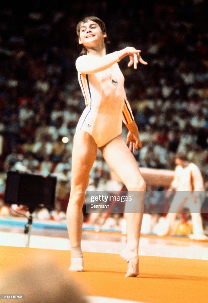 14 year old pixie gymnast from Romania Nadia Comaneci smiles and poses during her floor routine at the 1976 Summer Games in Canada Comaneci became...