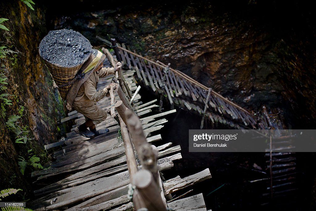 38 year old Prabhat Sinha, from Assam, carries a load of coal weighing 60kg's, supported by a head-strap, as he ascends the staircase of a coal mine on April 16, 2011 near the village of Khliehriat, in the district of Jaintia Hills, India. The Jaintia hills, located in India's far North East state of Meghalaya, miners descend to great depths on slippery, rickety wooden ladders. Children and adults squeeze into rat hole like tunnels in thousands of privately owned and unregulated mines, extracting coal with their hands or primitive tools and no safety equipment. Workers can earn as much as 150 USD per week or 30,000 Rupees per month, significantly higher than the national average of 15 USD per day. After traversing treacherous mountain roads, the coal is delivered to neighbouring Bangladesh and to Assam from where it is distributed all over India, to be used primarily for power generation and as a source of fuel in cement plants. Many workers leave homes in neighbouring states, and countries, like Bangladesh and Nepal, hoping to escape poverty and improve their quality of life. Some send money back to loved ones at home, whilst many others squander their earnings on alcohol, drugs and prostitution in the dusty, coal mining towns like Lad Rymbai. Some of the labor is forced, and an Indian NGO group, Impulse, estimates that 5,000 privately-owned coal mines in Jaintia Hills employed some 70,000 child miners. The government of Meghalaya refuted this figure, claiming that the mines had only 222 minor workers. Despite the ever present dangers and hardships, children, migrants and locals flock to the mines hoping to strike it rich in India's wild east.