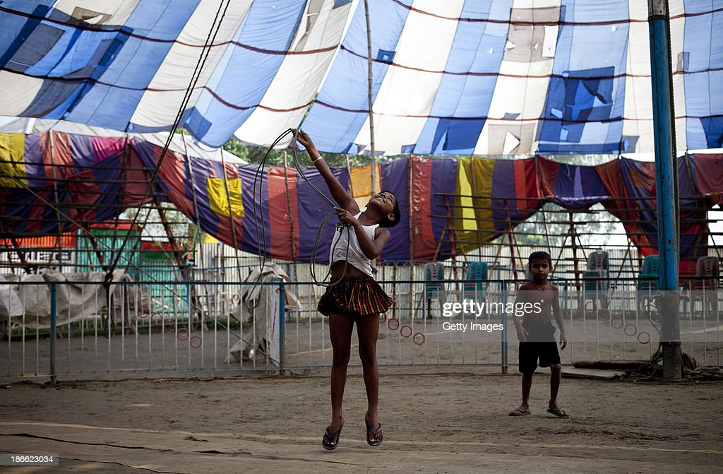 8 year old Puja Sarker goofs around during her free time in the morning before performing at the Olympic Circus, November 1, 2013 in Jamsha, Bangladesh. Puja was born into the circus, as were her parents, and never had the chace to attend school. Generations of low income families are born into circuses with rarely the hope of ever working in different profession or escaping the harsh realities of the circus. The children, often very young, are trained to be full working members usually without the opportunity for an education. As modernization slowly takes over landscape of Bangladesh, the circus is a dying art form and is moving further and further away from mainstream entertainment.