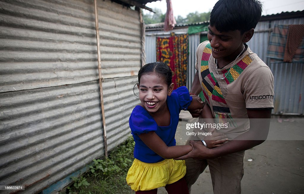 8 year old Puja Sarker goofs around with her brother in law in the residential area of the Olympic Circus, October 31, 2013 in Jamsha, Bangladesh. Puja was born into the circus, as were her parents, and never had the chance to attend school. She performs in the circus spinning with hula hoops. Generations of low income families are born into circuses with rarely the hope of ever working in different profession or escaping the harsh realities of the circus. The children, often very young, are trained to be full working members usually without the opportunity for an education. As modernization slowly takes over landscape of Bangladesh, the circus is a dying art form and is moving further and further away from mainstream entertainment.