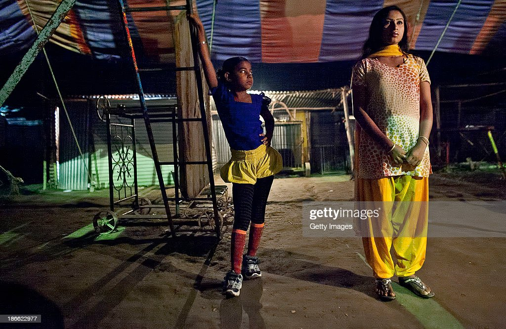 8 year old Puja Sarker looks at an older circus worker before she performs at the Olympic Circus, November 1, 2013 in Jamsha, Bangladesh. Puja was born into the circus, as were her parents, and never had the chance to attend school. Generations of low income families are born into circuses with rarely the hope of ever working in different profession or escaping the harsh realities of the circus. The children, often very young, are trained to be full working members usually without the opportunity for an education. As modernization slowly takes over landscape of Bangladesh, the circus is a dying art form and is moving further and further away from mainstream entertainment.