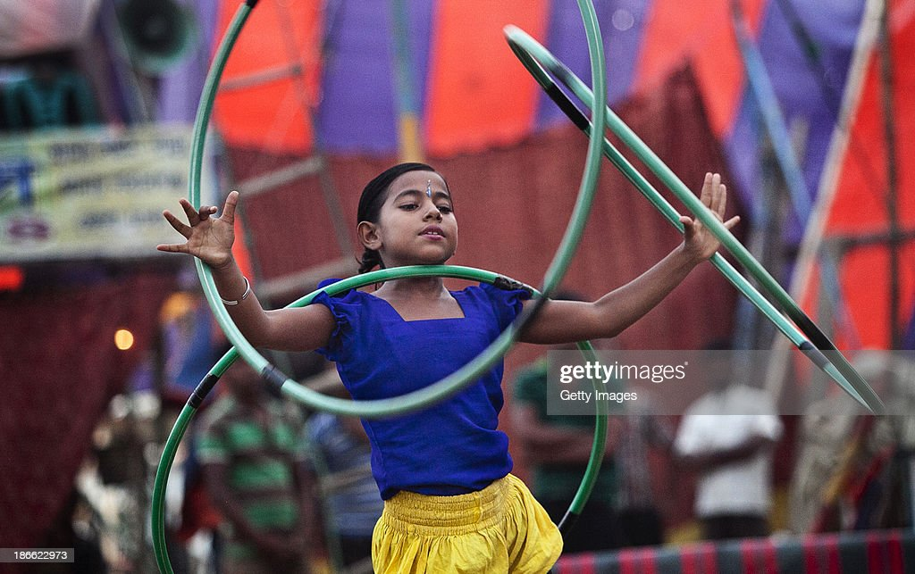 8 year old Puja Sarker performs at the Olympic Circus, November 1, 2013 in Jamsha, Bangladesh. Puja was born into the circus, as were her parents, and never had the chance to attend school. Generations of low income families are born into circuses with rarely the hope of ever working in different profession or escaping the harsh realities of the circus. The children, often very young, are trained to be full working members usually without the opportunity for an education. As modernization slowly takes over landscape of Bangladesh, the circus is a dying art form and is moving further and further away from mainstream entertainment.