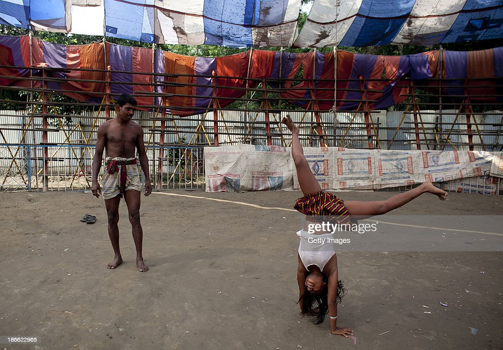 8 year old Puja Sarker practices performing with Mohammad Moshroom, before working in the Olympic Circus, November 1, 2013 in Jamsha, Bangladesh. Puja was born into the circus, as were her parents, and never had the chace to attend school. Generations of low income families are born into circuses with rarely the hope of ever working in different profession or escaping the harsh realities of the circus. The children, often very young, are trained to be full working members usually without the opportunity for an education. As modernization slowly takes over landscape of Bangladesh, the circus is a dying art form and is moving further and further away from mainstream entertainment.