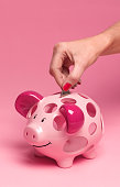 40 year old putting coin in piggy bank
