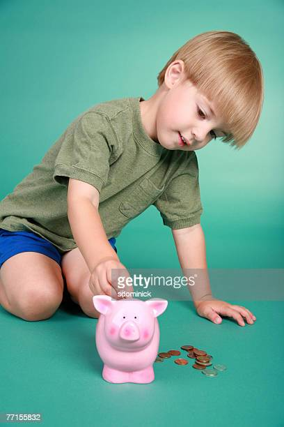 3 1/2 year old putting money into a piggy bank