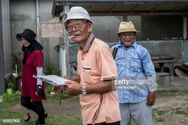 74 year old retiree Tashikatsu Suzuki keeps score during a game of ground golf on August 10 2014 in Omaezaki Japan The town of Omaezaki is living in...