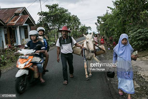 42 year old Ridwan Sururi accompanied by his daughter Indriani Fatmawati and Luna a horse used as mobile library walk to Miftahul Huda Islamic...