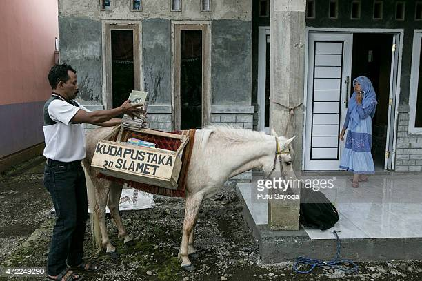 42 year old Ridwan Sururi loads books onto a horse used as a mobile library on May 5 2015 in Serang Village Purbalingga Central Java Indonesia Ridwan...
