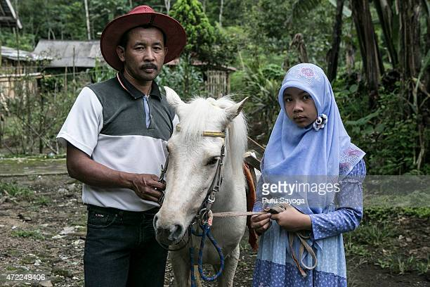 42 year old Ridwan Sururi posses for a portrait with his daughter Indriani Fatmawati and Luna a horse used as mobile library on May 5 2015 in Serang...