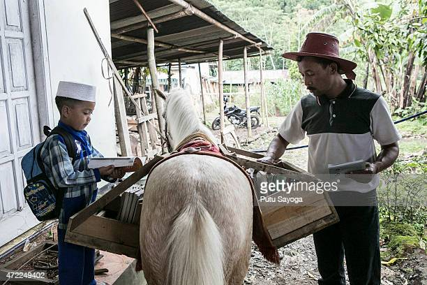 42 year old Ridwan Sururi prepares the books while a boy selects book at the mobile library on May 5 2015 in Serang Village Purbalingga Central Java...