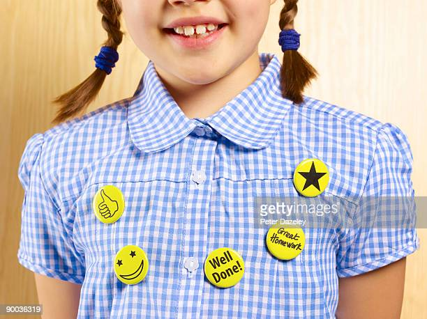 8 year old school girl with reward button badges.