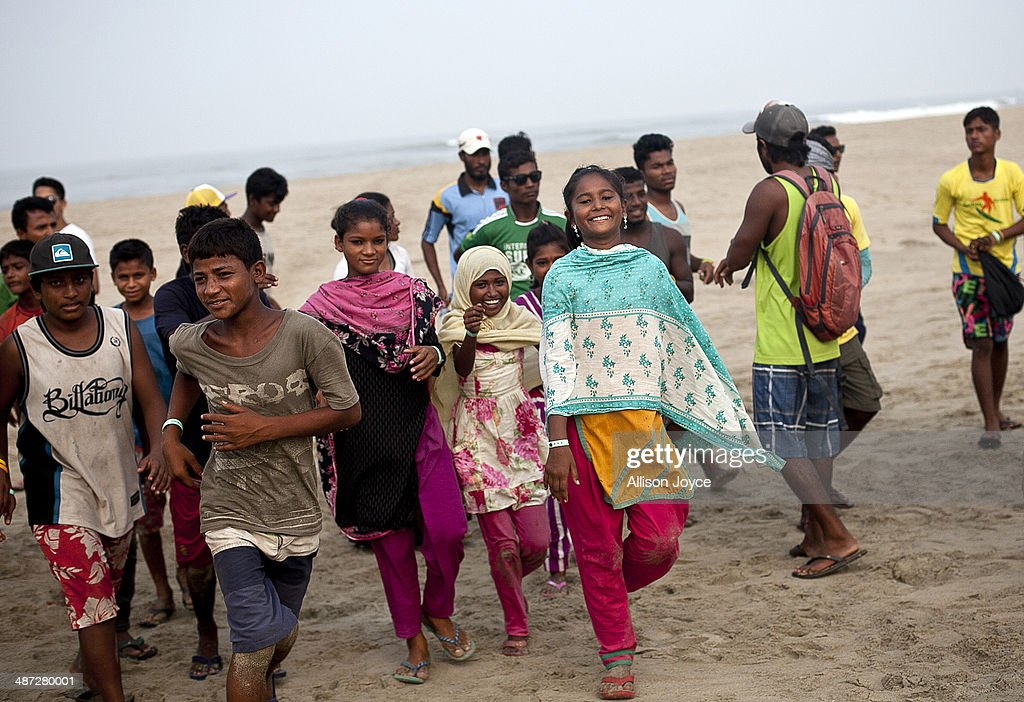 COX'S BAZAR, BANGLADESH - APRIL 24: 12 year old Shuma, 10 year old Jahanara, and 12 year old Shumi are seen with other surfers after posing for a group photo at the Cox's Bazar annual surf competition April 24, 2014 in Cox's Bazar, Bangladesh. A group of 10-12 year old female beach vendors, most of whom have dropped out of school to help support their families, have been learning to surf for the past three months in preparation for the annual Cox's Bazar surf competition. 24 year old surfer, lifeguard and beach worker Rashed Alam, has been teaching and mentoring the girls for 3 months. Like the girls, Alam dropped out of school and started working on the beach to help support his family at a young age. He started surfing when he was 16. He says that his way of giving back is by ensuring that girls get a good future through surfing.