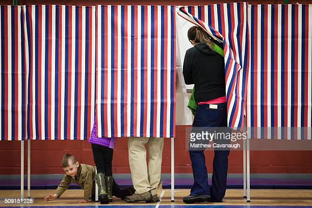 3 year old Simon Desmarais crawls beneath voting booths as his parents Ashley Grover and Andrew Desmarais cast their votes on February 9 2016 at...